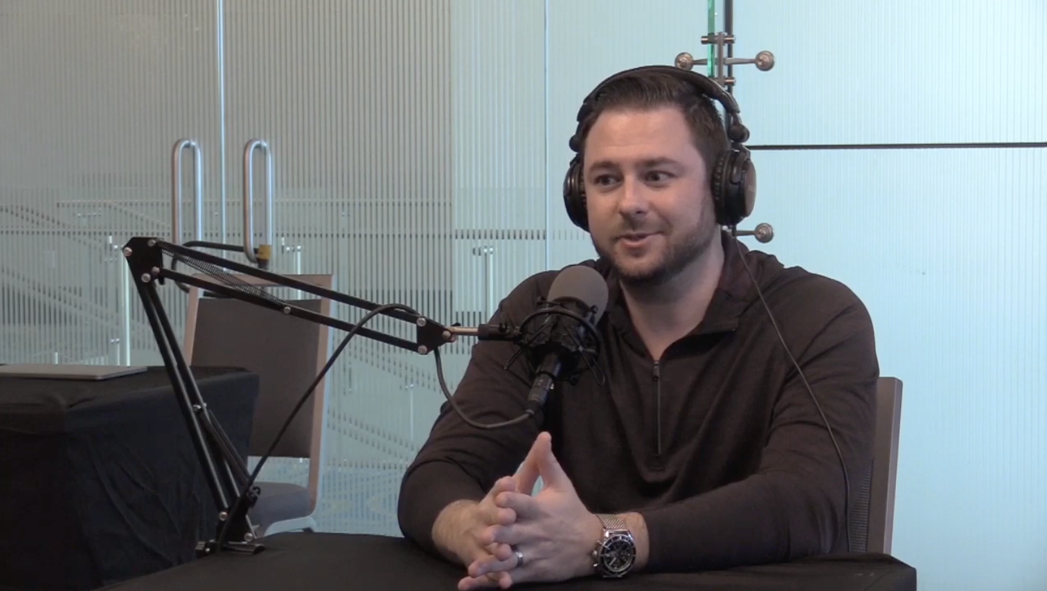 Criminal defense attorney Adam sits at a desk with headphones and a microphone while he's interviewed on a podcast