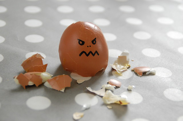 an egg with an angry face drawn on is cracked open on a table. The article is about a fight over breakfast turned into an arrest.