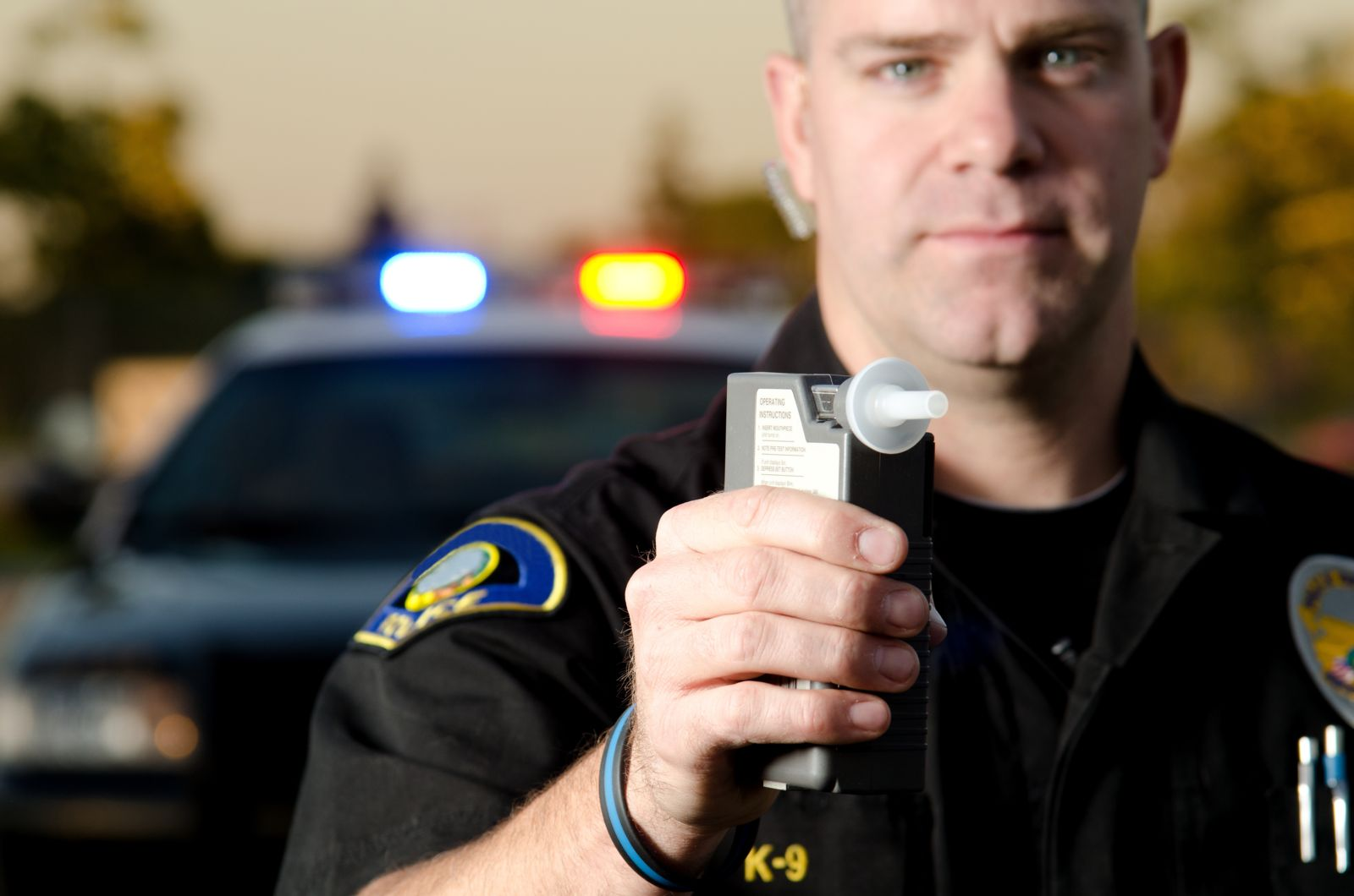 A police officer holds out a breathalyzer to test someone as part of a DUI arrest. His police car with lights on is behind him.