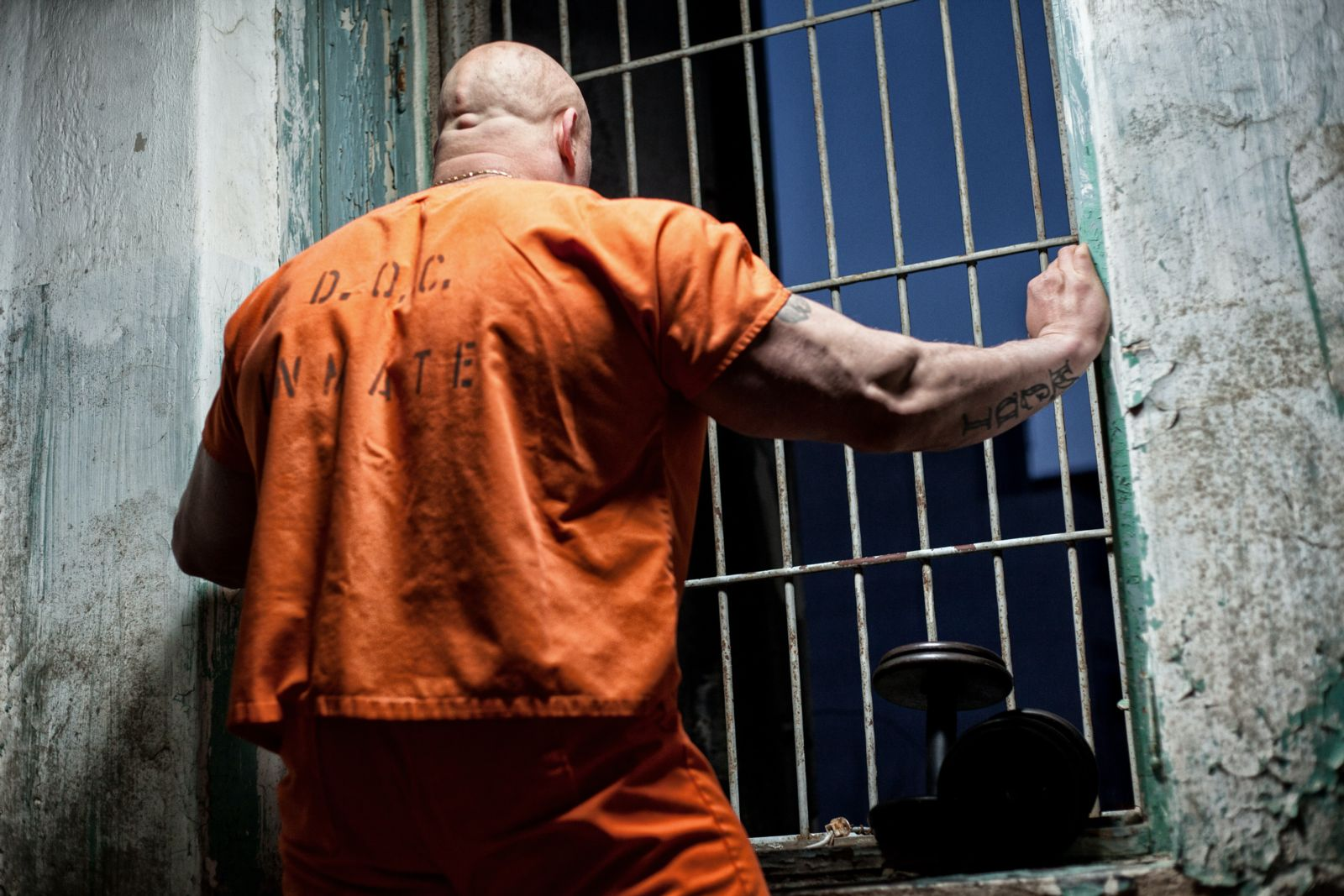 Florida Prison inmates are dying from Covid -19 at the highest rate in the country - a man in a prison uniform is in a prison cell in this image