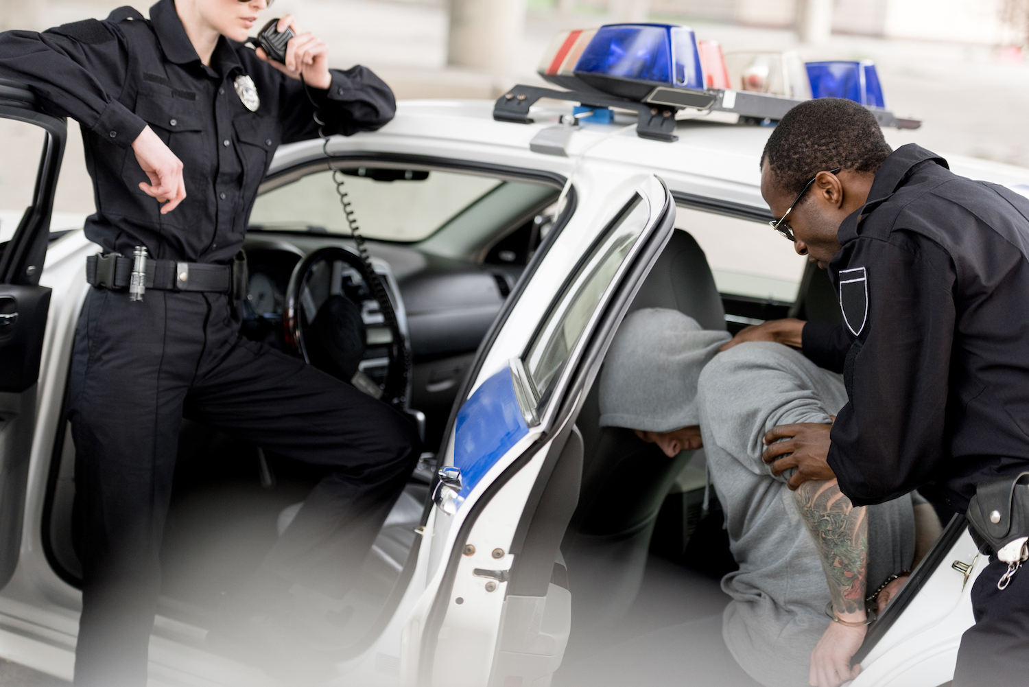 woman and man cop put a man they arrested in Fort Lauderdale in the back of their car under arrest