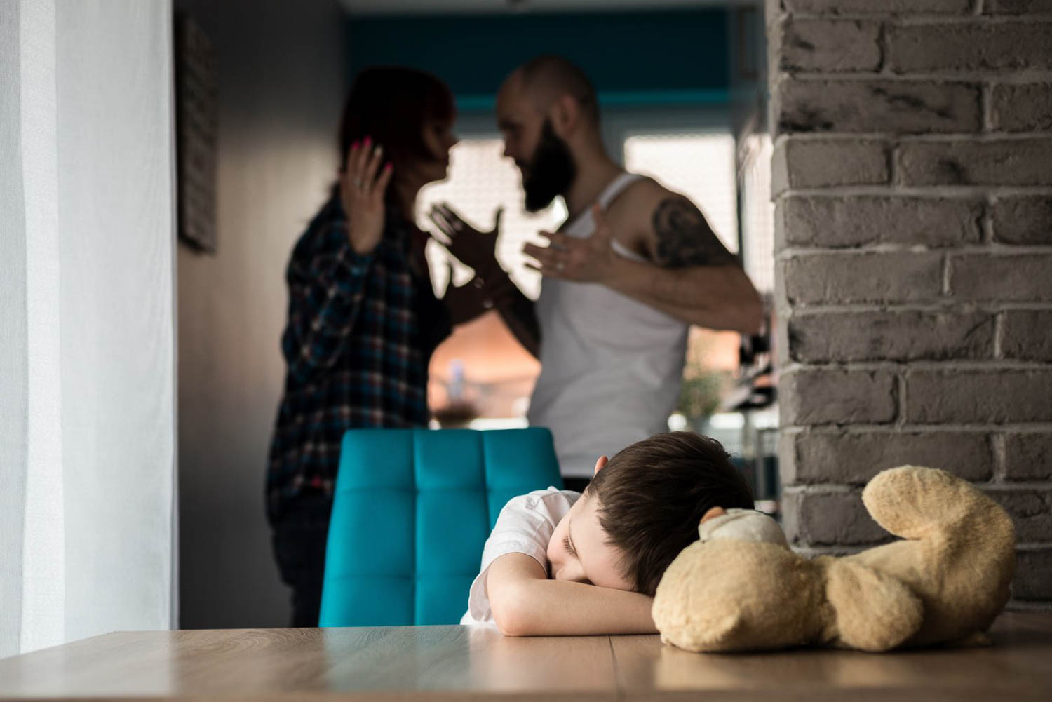 in the image, a man and woman are fighting in a hallway while a child is sitting at a dining room table with his head on his arms on the table with his teddy bear. The image is meant to depict a domestic violence situation in Fort Lauderdale, South Florida