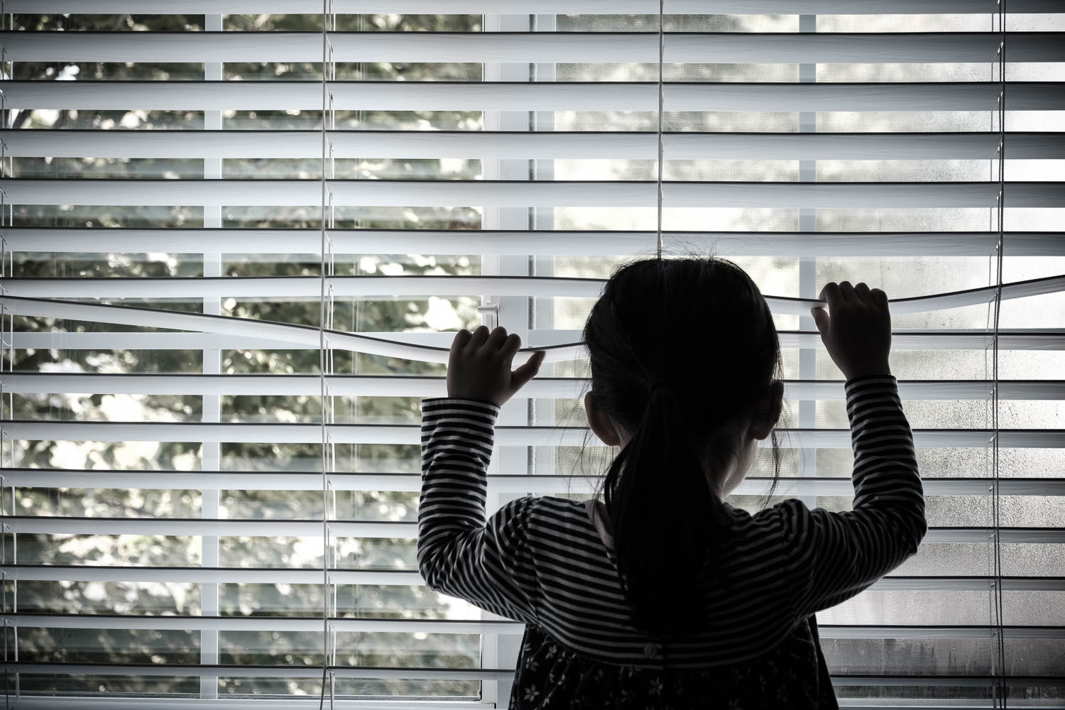 A fort lauderdale child looks outside between the blinds in her south florida home. She is probably about 4 years old, and would be eligible for exploited children civl remedies
