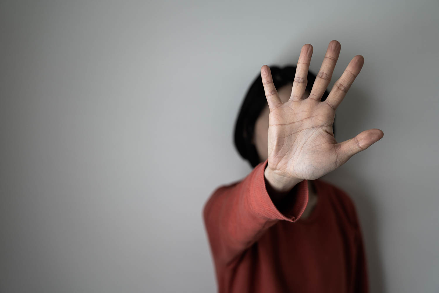 A woman stand against a wall with her hand in front of her face. mandatory reporting guidelines in Florida for Sexual battery and abuse