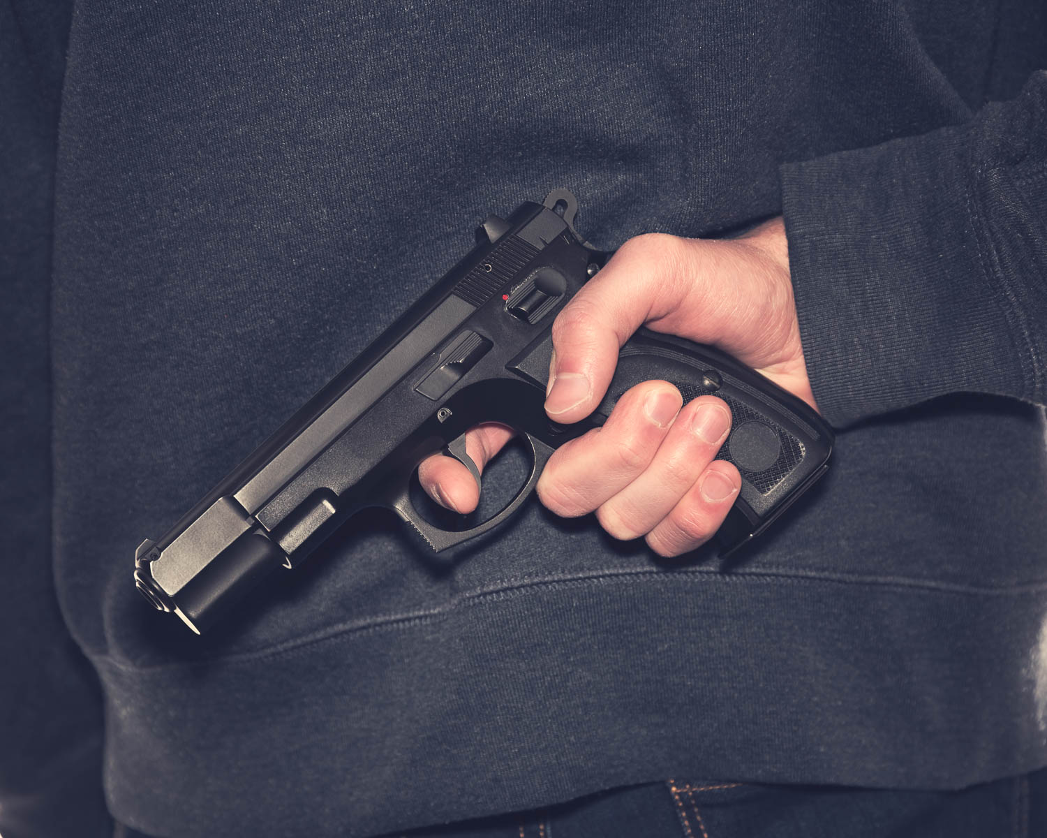a person holds a hand gun, hidden, behind their back in South Florida. This could be considered a serious crime