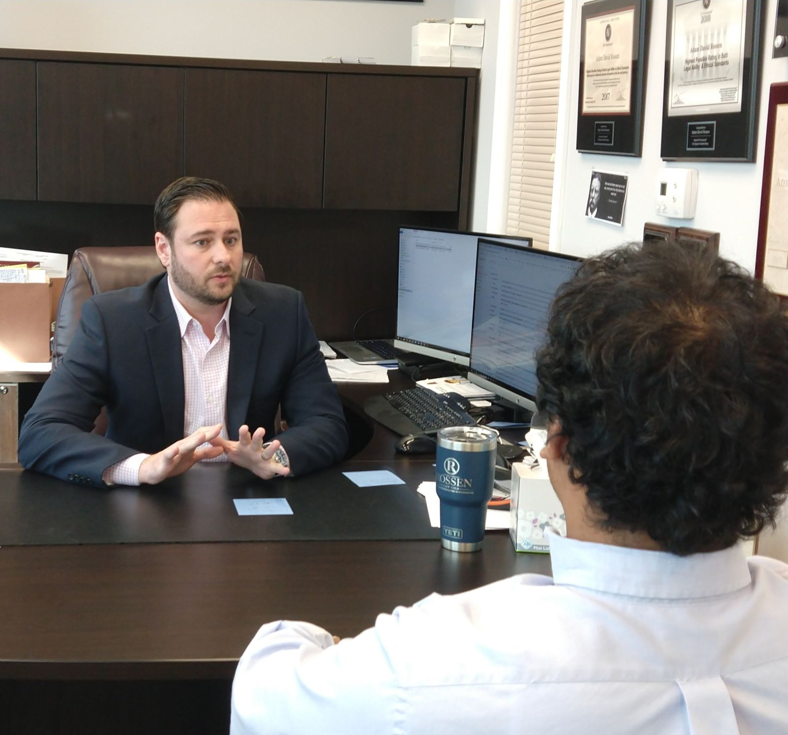 Adam Rossen at the Rossen law firm speaks with a client in his criminal defense law firm office in Fort Lauderdale during a free strategy session