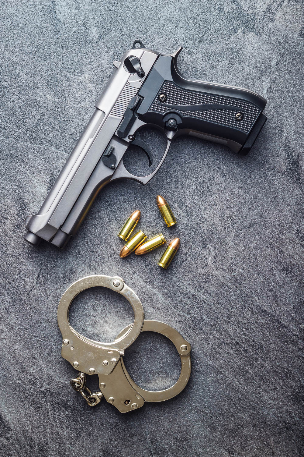 a gun, bullets and handcuffs are out on a table in south florida. Gun and weapon crimes are serious in Florida. A Fort Lauderdale Criminal Defense Attorney can help defend your rights and your future.