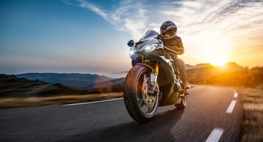 motorcycle rider on coastal road at sunset