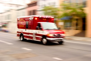 blurred image of ambulance driving on urban road