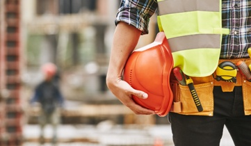 Construction Worker Holding an Orange Hard Hat on a Construction Site