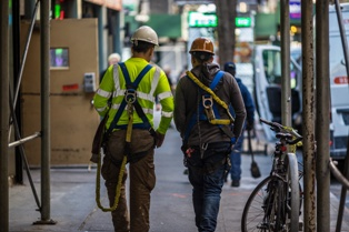 Two Construction Workers Walking Down a New York City Sidewalk Hofmann & Schweitzer