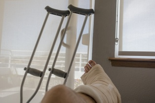 Injured Victim Sitting on the Couch With Crutches
