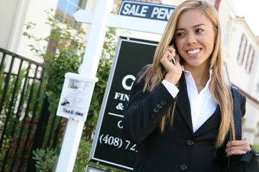 Real Estate Agent in Front of a Sale Pending Sign