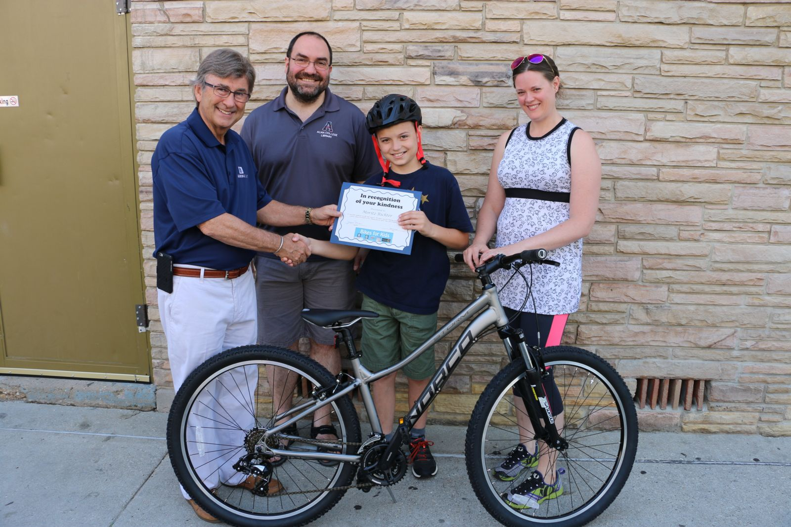 Joe presents Moritz Richter with his Bikes for Kids certificate. Marcus, Moritz's father, and Allison Quast-Lents, owner of Motorless Motion, helped Moritz pick out his mountain bike. Bikes for Kids 2016