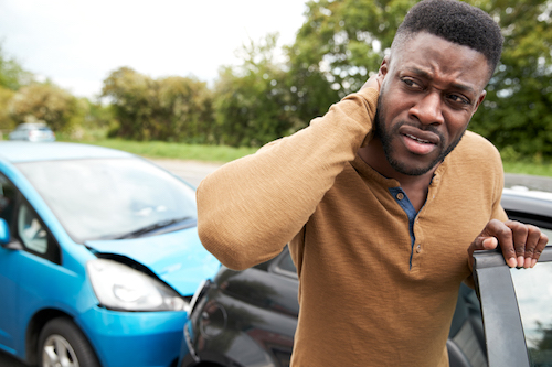 A man's hand is on his neck after getting whiplash in a Florida Car Accident. He was rear ended by another car on the road. The other driver does not have insurance. A Florida Car Accident Attorney can help.