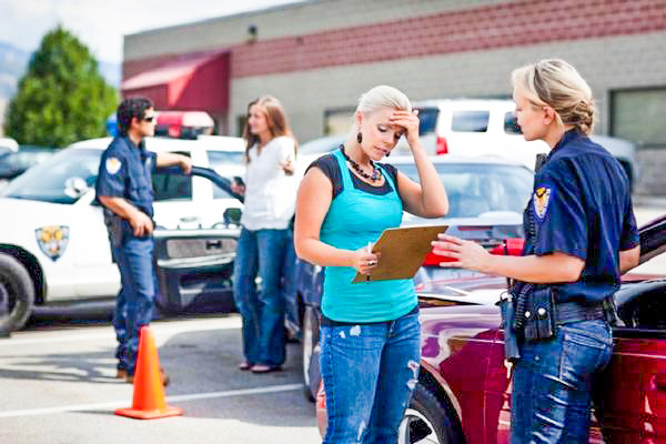 The picture shows two women in the Sawgrass Mills Mall Parking lot after a car accident. The Fort Lauderdale women are talking to police officers and filing out accident reports. Florida Car Accident Attorney at Rosenberg Law Firm can help