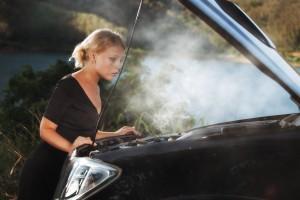 Woman looking at a smoking car engine