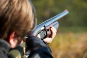 Boy with firearm aiming in the distance