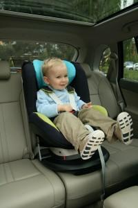 Toddler boy properly restrained in car seat