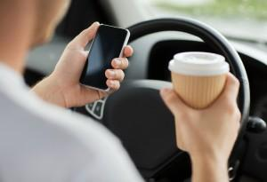 Driver using cell phone and drinking coffee