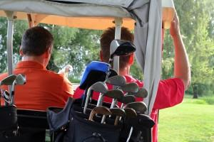 golfers driving golf cart
