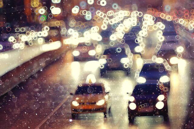 Cars lane changing in rainy traffic