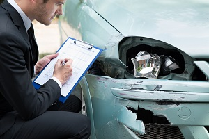 Insurance adjuster evaluates a car to assess the damage from a collision