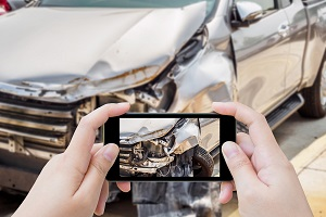 A woman uses her smartphone to take pictures of her car crash scene