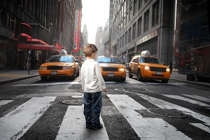 A young child attempts to cross the street at a busy intersection