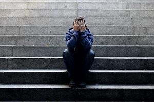 Depressed young man sits on outdoor staircase, his face covered by his hands