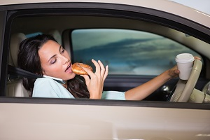 Woman is distracted by trying to eat and talk on the phone while driving a car