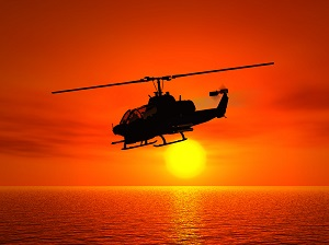 A helicopter flies over water at sunset