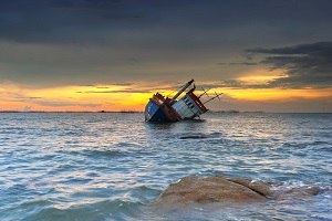 Wrecked ship is listing in the sea at sunset