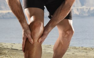 Runner holding his knee due to pain