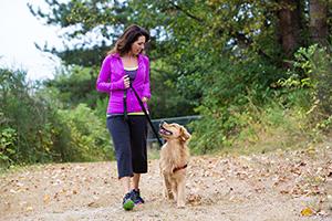 Happy woman walking dog