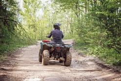 Male Riding an ATV on a Dirt Trail