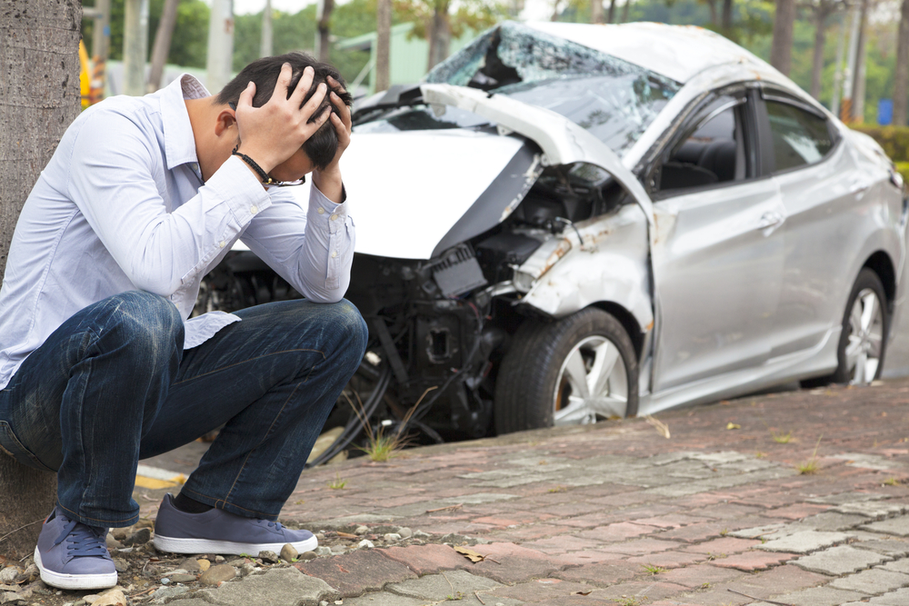 Man holding head in front of car wreck