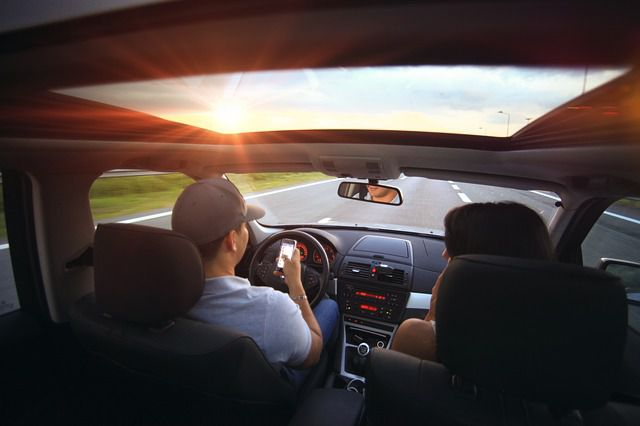 two people in the front seat of a car on the road