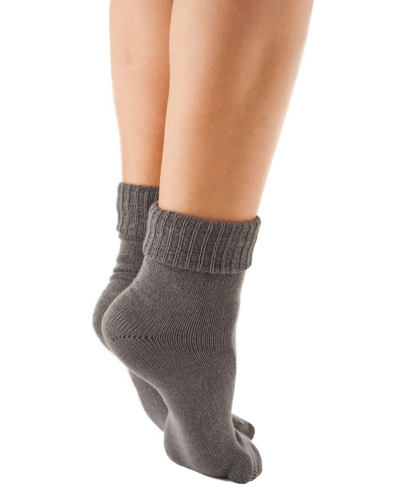 teen in gray socks standing on tiptoes