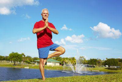 Older man practicing yoga outside