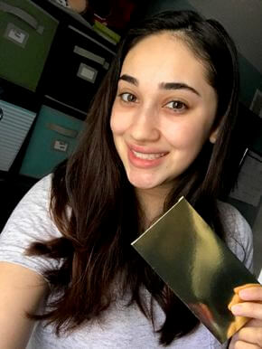 Woman holding golden envelope while smiling