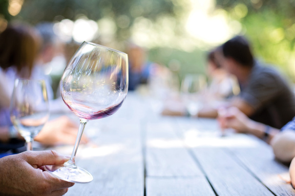 Hand holding wine glass, people drinking wine in background