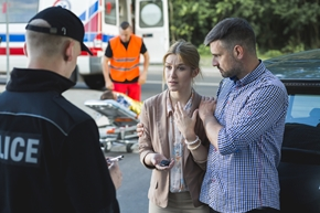 Two witnesses talking to police at an accident scene
