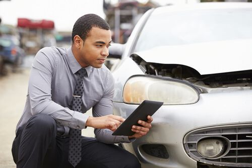 An insurance adjuster examines the damage a car suffered in an accident.