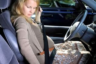 Pregnant woman buckling seat belt