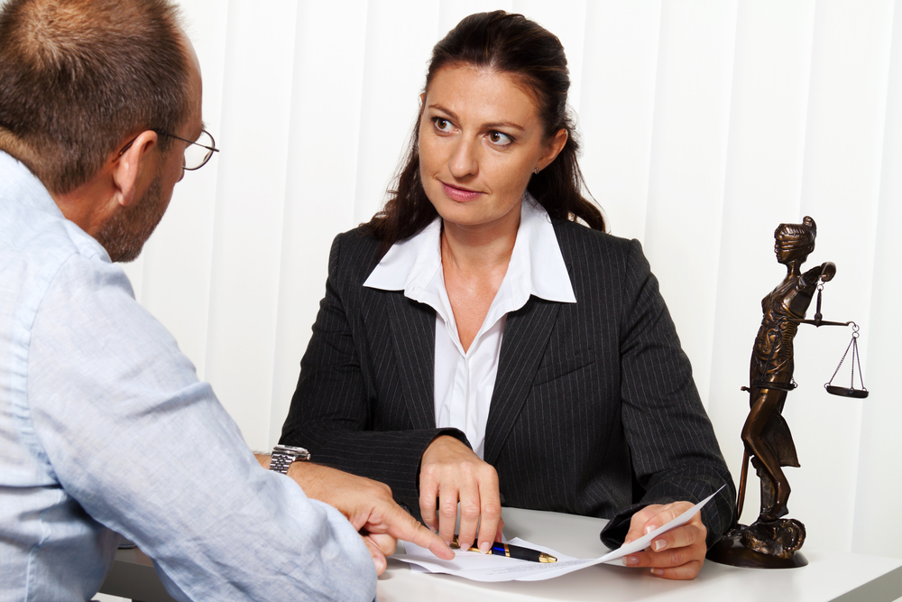 Man discussing papers with an attorney