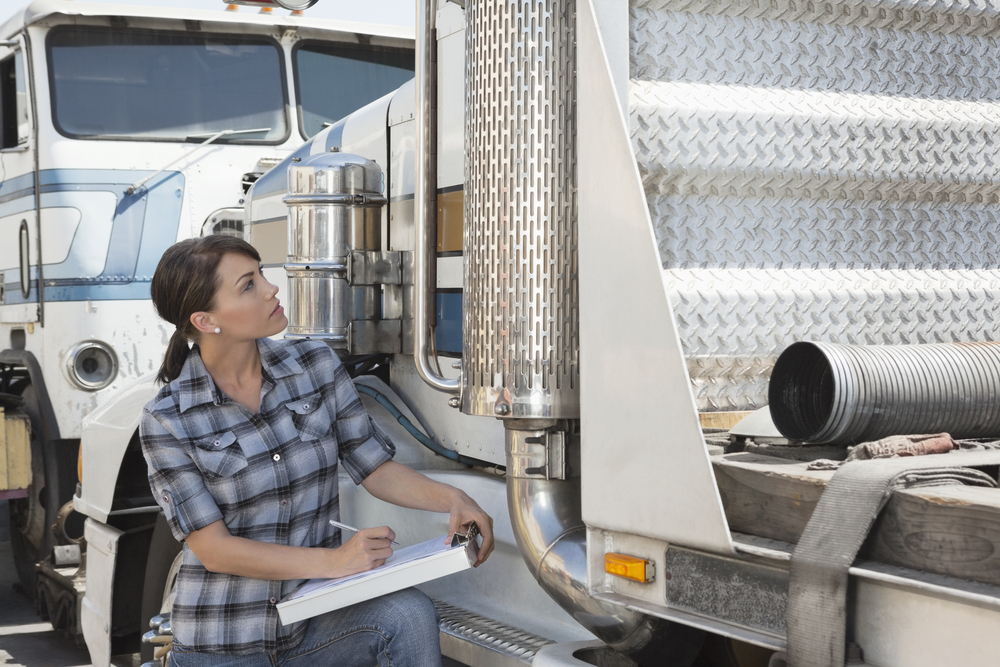 Truck driver inspecting her truck