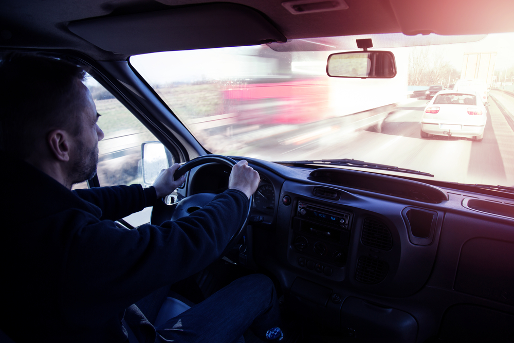 Truck driver behind wheel in traffic