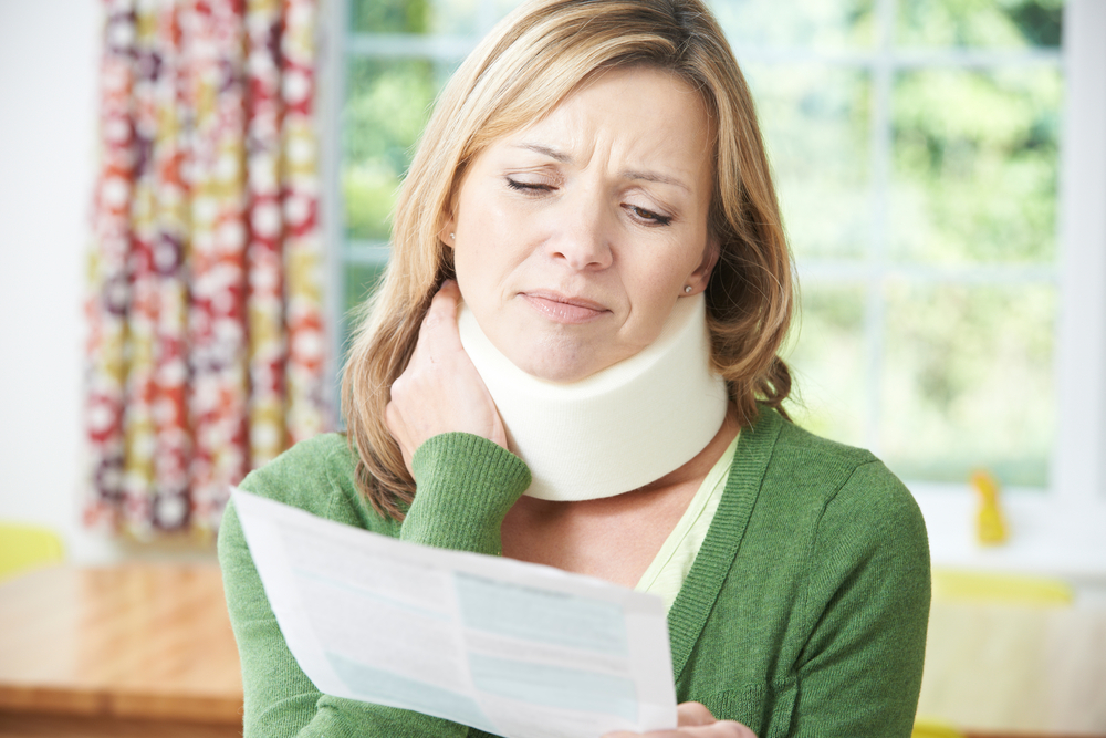 Woman wearing neck brace suffering with pain