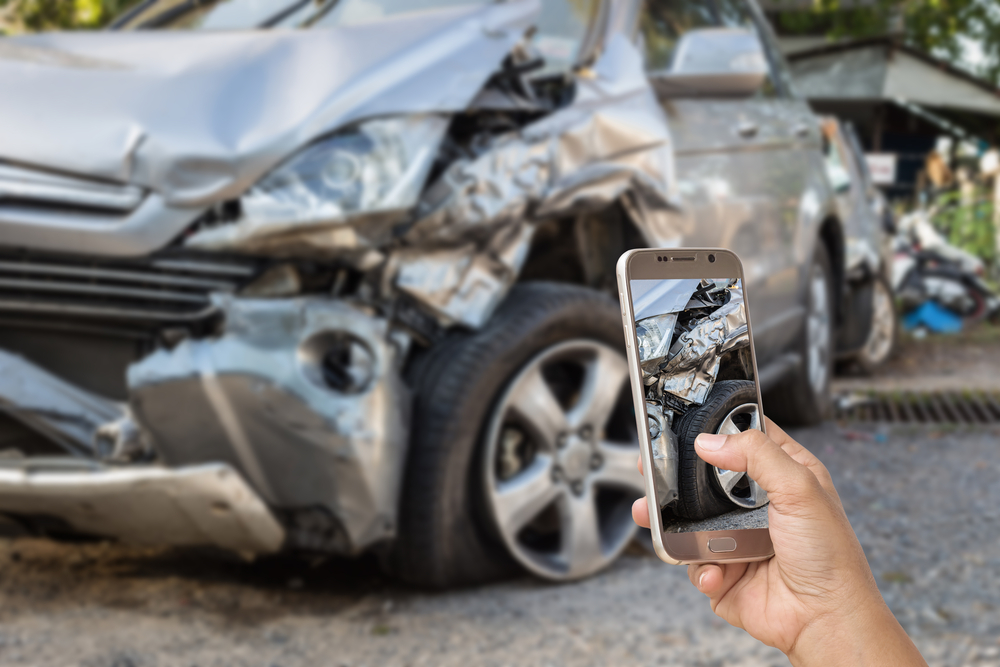 Woman taking photo of smashed car with cell phone